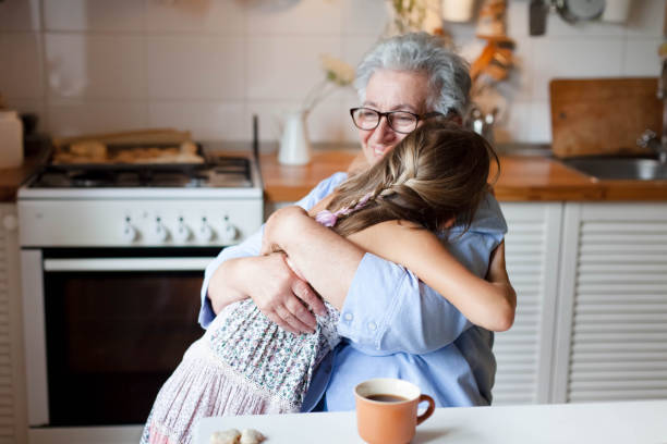 Grandmother hugging granddaughter. Child girl and elderly senior woman in cozy home kitchen. stock photo