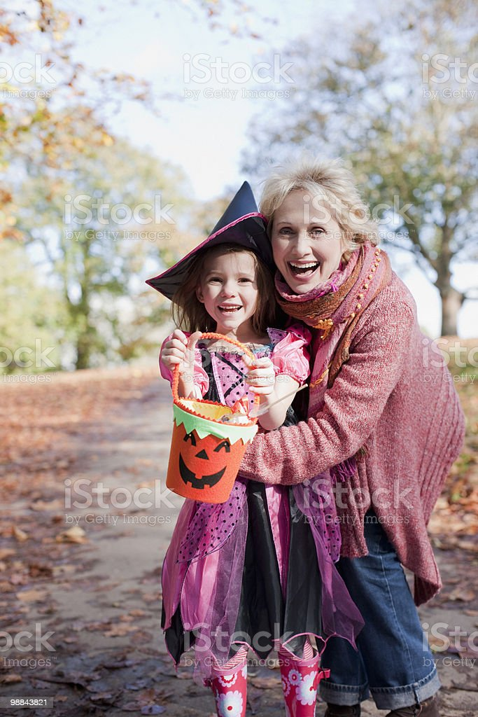 Grandmother hugging granddaughter in Halloween costume royalty-free stock photo