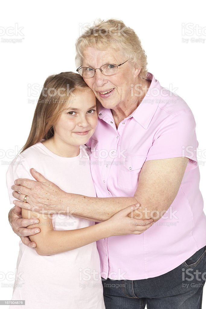 Grandmother hugging granddaughter wearing pink isolated on white. royalty-free stock photo