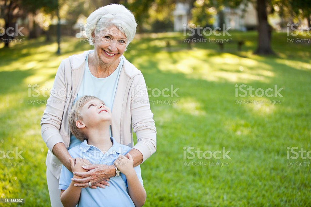Grandmother hugging grandson stock photo