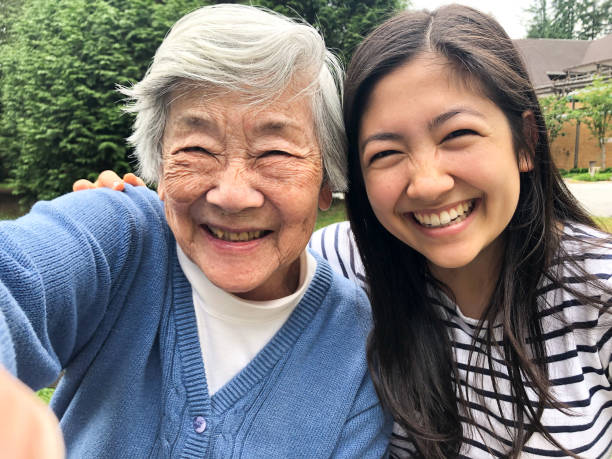 Grandmother in 90s Taking Selfie with Granddaughter Outside Retirement Home stock photo