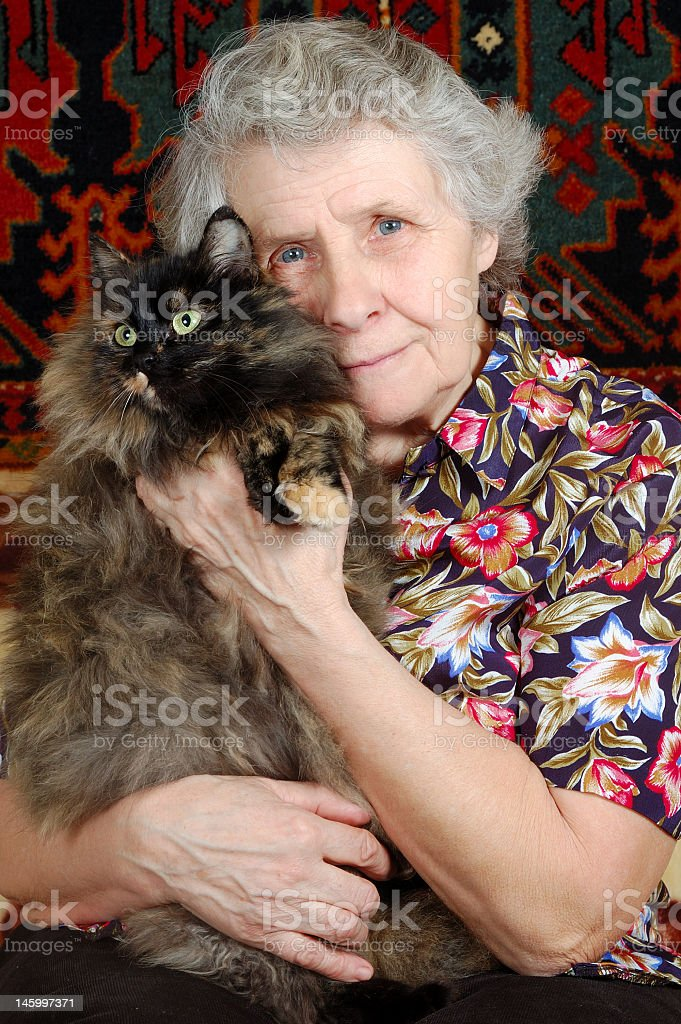 Grandmother in floral shirt holding her cat royalty-free stock photo