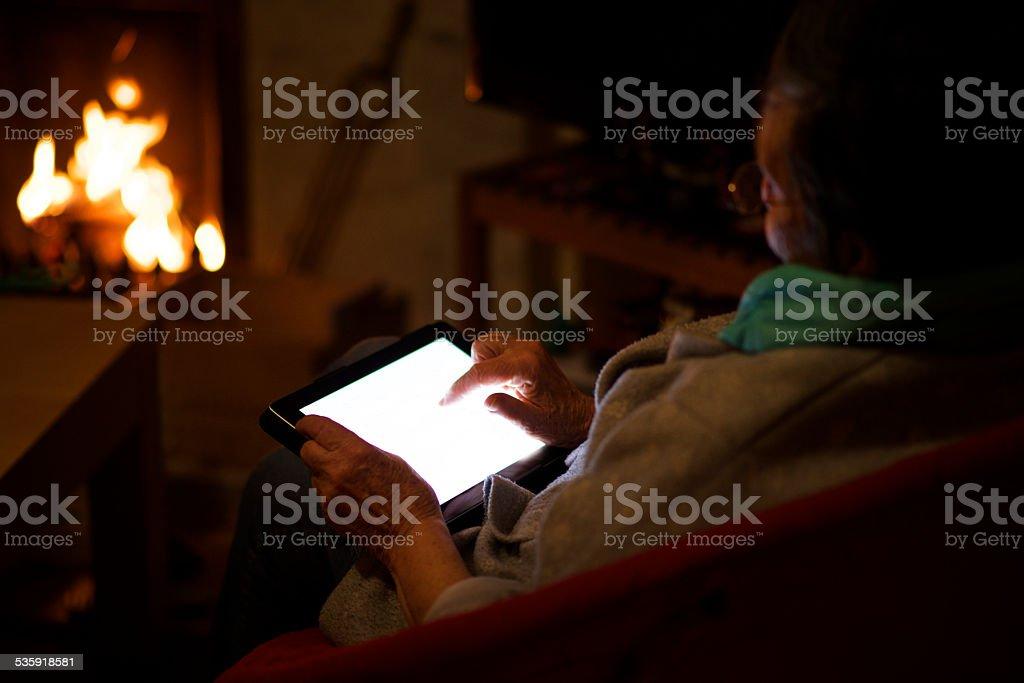 Großmutter vor dem Kamin mit seinem tablet – Foto