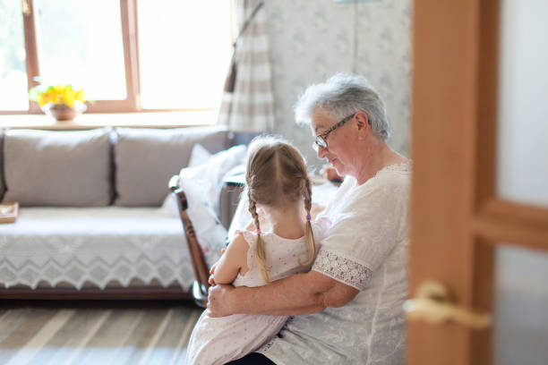 Grandmother is hugging granddaughter in cozy home living room. Kind senior woman is telling story or fairy tale to cute little child girl. Kid is enjoying warm hands, care, support and consolation. stock photo