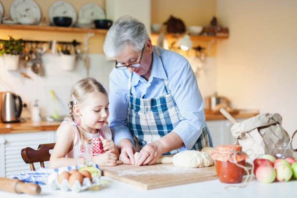 Grandmother is teaching kid to cook pastries and bread in cozy kitchen at home. stock photo