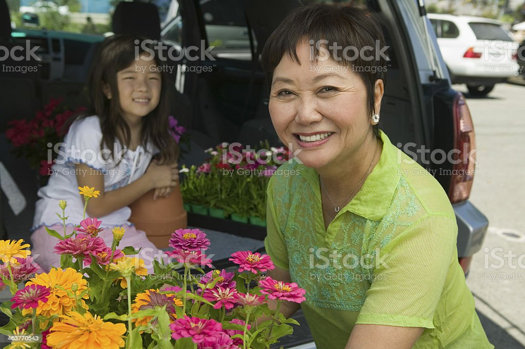 Grandmother Loading Various Flowers In Car royalty-free stock photo