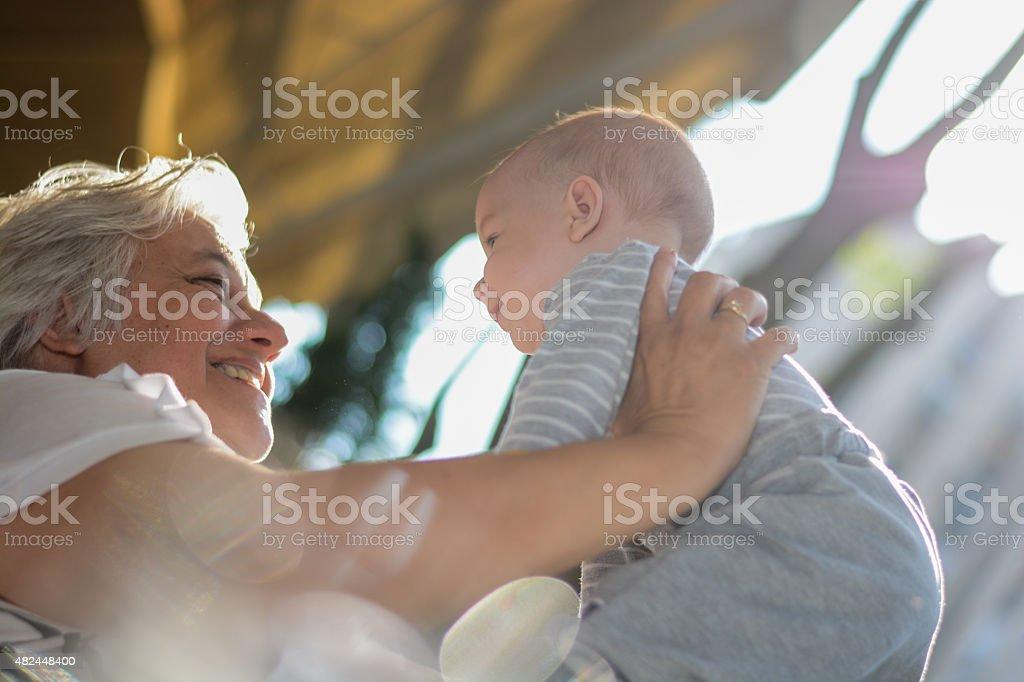 Abuela examinar niño bebé con una sonrisa. - foto de stock