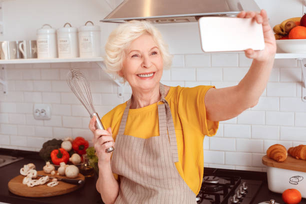 Grandmother makes selfie with a whisk in the kitchen. stock photo