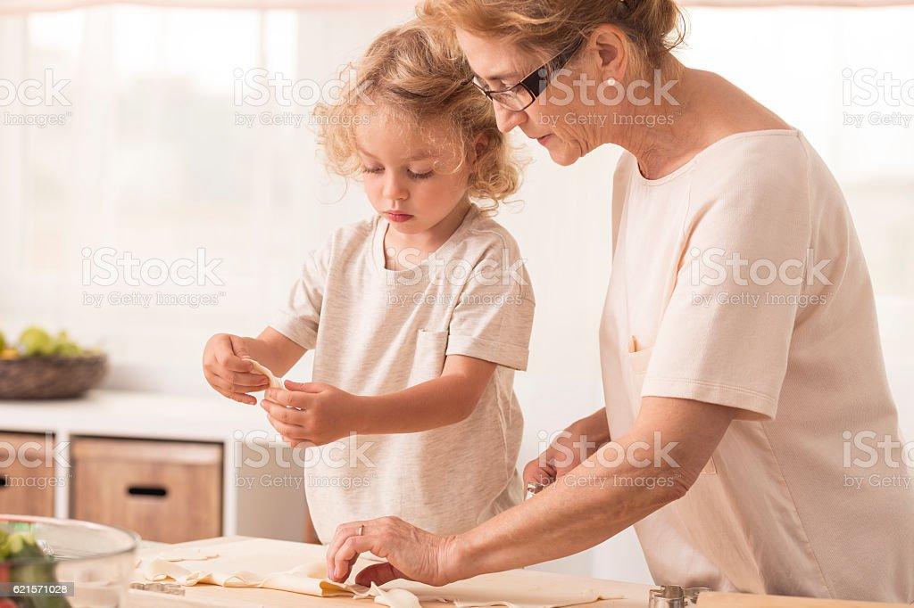 Grandmother making cookies with grandchild photo libre de droits