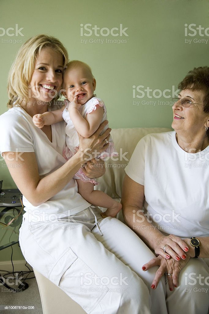 Grandmother, mother and baby girl (9 months) on sofa foto de stock libre de derechos