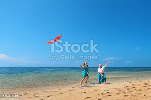 849648098 istock photo Grandmother, mother, and child launching kite on sea beach 579418086