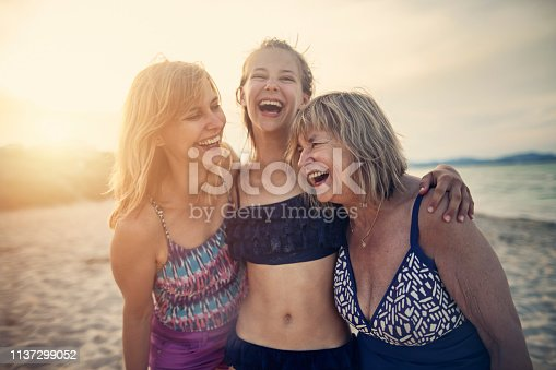 Three generations - Grandmother, mother and daughter enjoying time together on the beach. Women are laughing happily and embracing.  Nikon D850