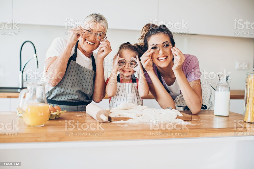 Grandmother, mother and daughter having fun in the kitchen stock photo