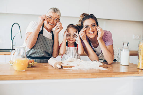 grandmother, mother and daughter having fun in the kitchen - mothers day stock photos and pictures
