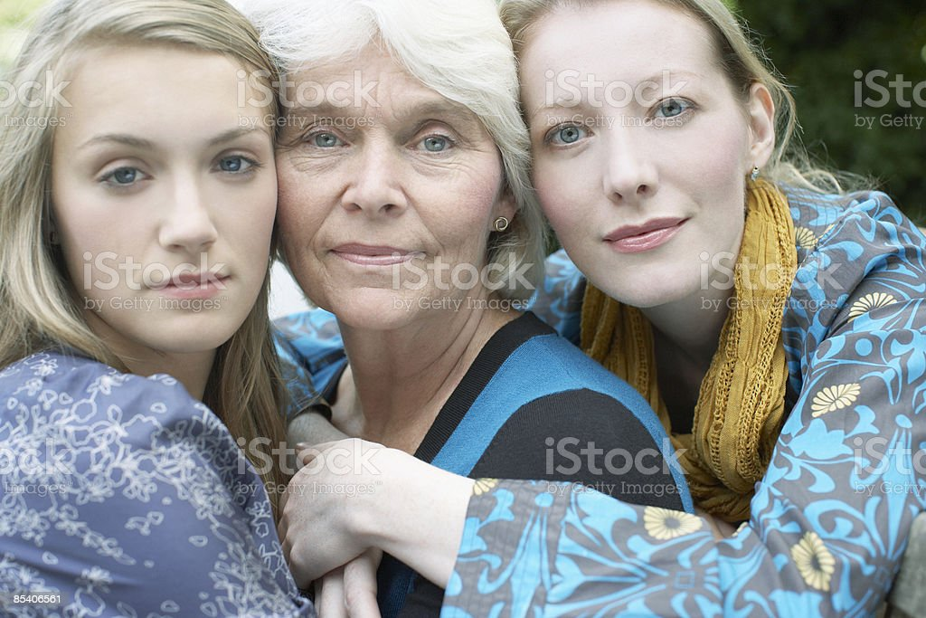 Grandmother, mother and daughter hugging stock photo