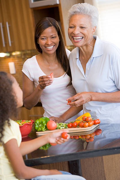 Grandmother, Mother And Daughter Preparing Meal Together stock photo