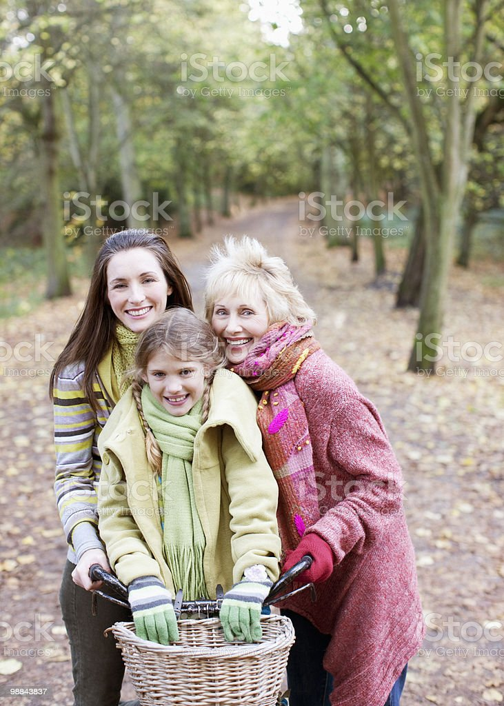 Grandmother, mother and daughter riding bicycles in park 免版稅 stock photo