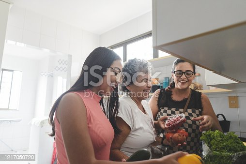 istock Grandmother, mother and daughter unpacking groceries in the kitchen 1217050720