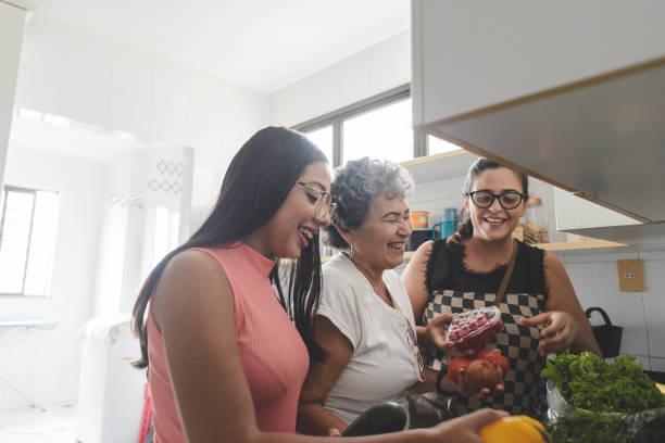 nonna, madre e figlia disfare la spesa in cucina - cucinare foto e immagini stock