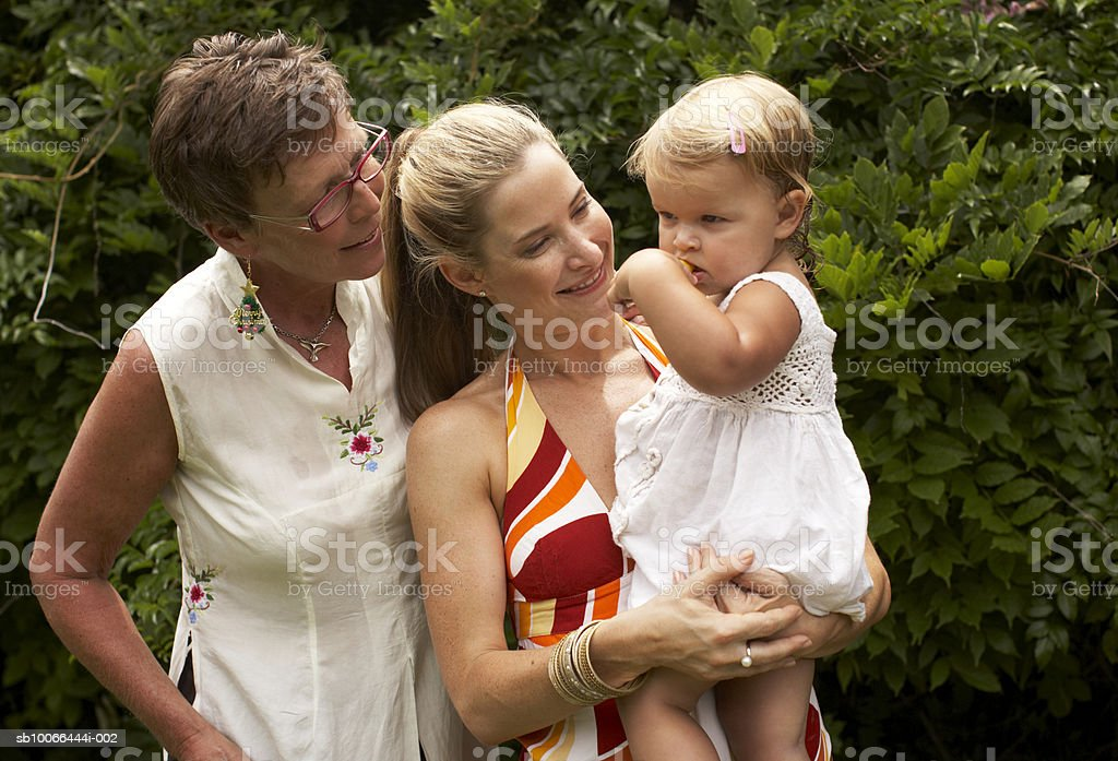 Grandmother, mother, and granddaughter (20-24 months) in yard royalty-free stock photo