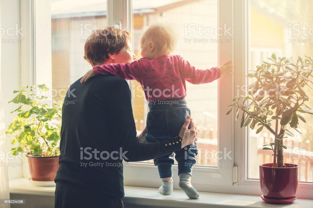 abuela jugando y cuidando niños en casa - foto de stock