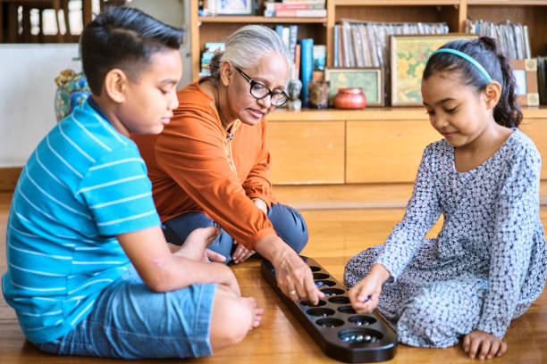 Grandmother playing games with her grandchildren at home stock photo