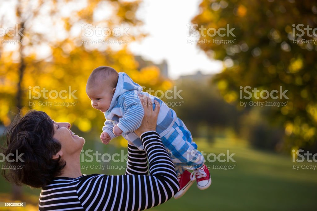 Grandmother playing in the park with her newborn baby grandchild stock photo