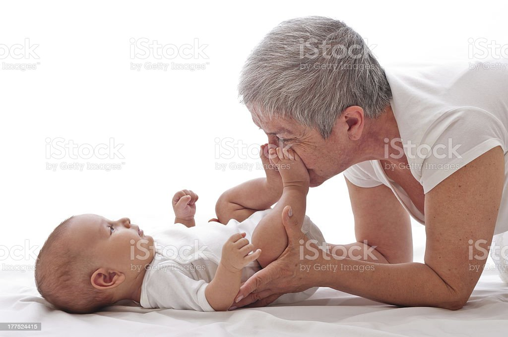 Grandmother playing with a baby stock photo