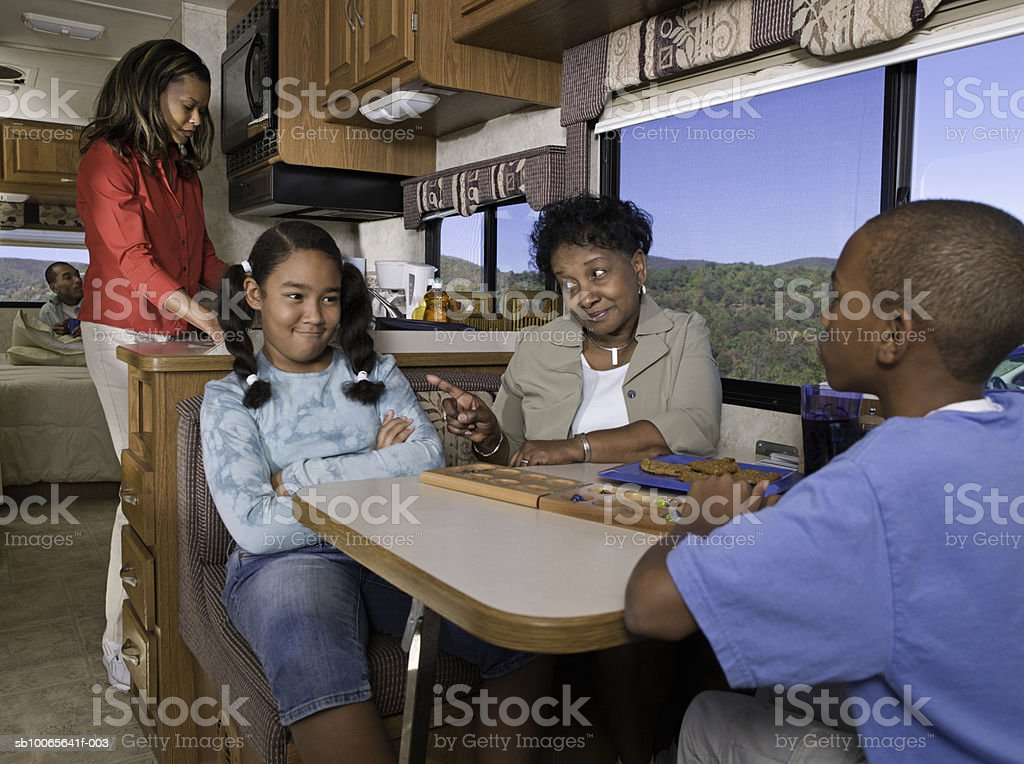 Grandmother playing with children (10-13) mother cooking in background in motorhome royalty-free stock photo