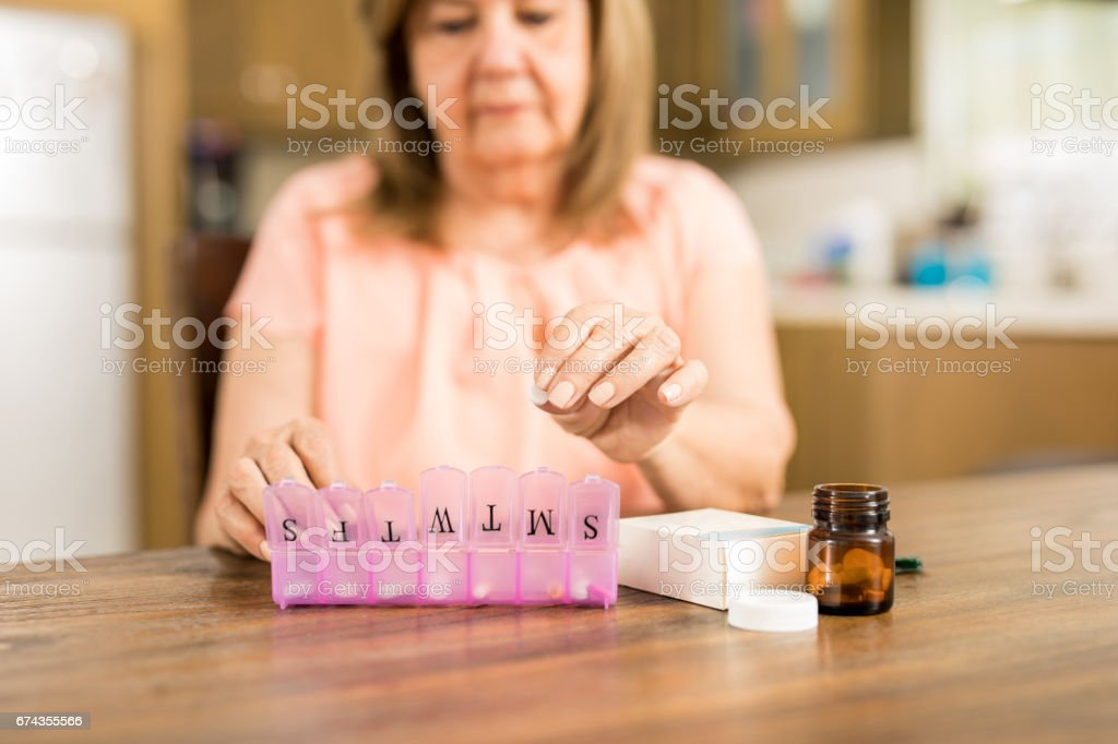 Grandmother putting tablets on a pill box stock photo