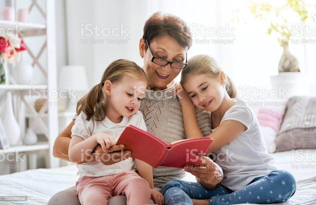Großmutter, einem Buch, Enkelinnen – Foto