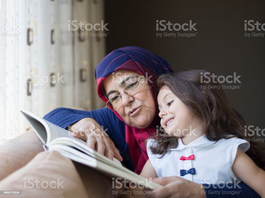 Grandmother reading a book with grand daughter stock photo