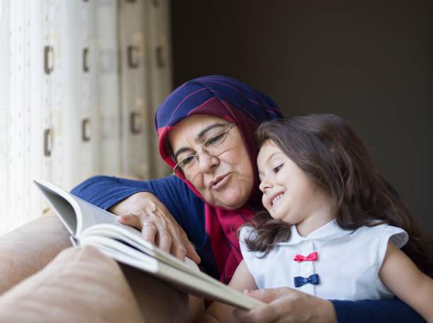 lecture d'un livre avec la petite-fille de grand-mère - jeunes arabes photos et images de collection