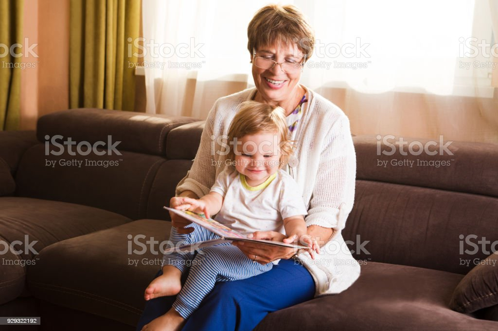 Grandmother reading a tale to her baby granddaughter. Family Reading Leisure stock photo