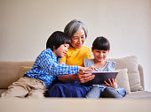 A Taiwanese grandmother reads from an electronic tablet to her grandchildren in a home in Taipei.