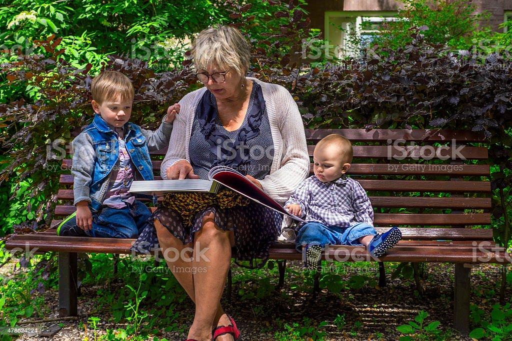 Abuela lectura a sus nietos - foto de stock