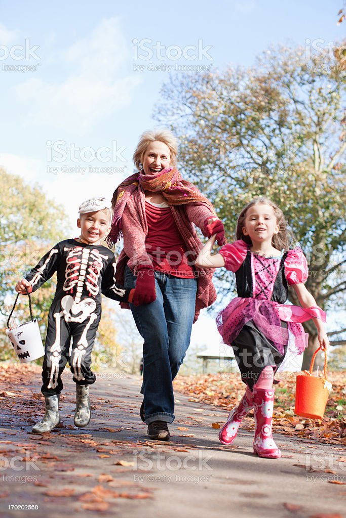 Grandmother running with grandchildren in Halloween costumes royalty-free stock photo