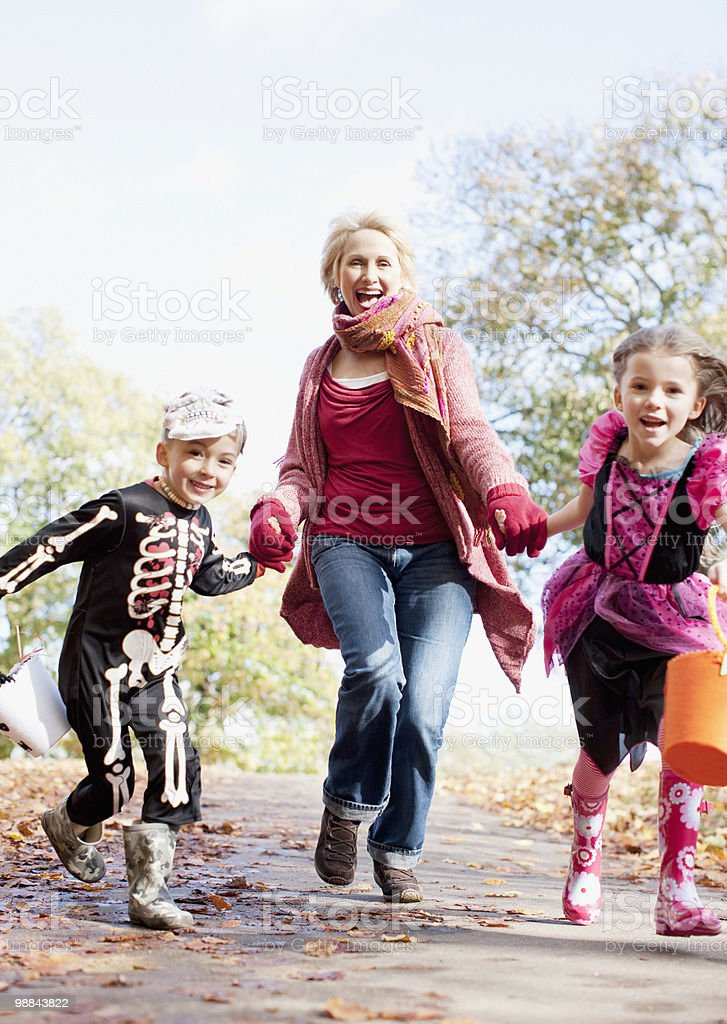Grandmother running with grandchildren in Halloween costumes royalty free stockfoto