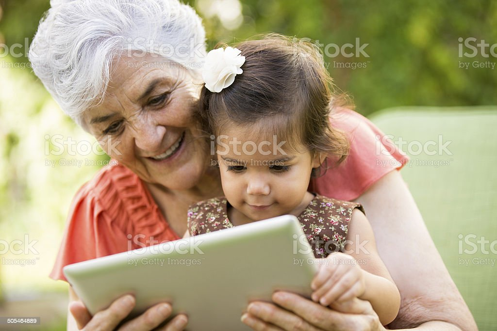 Grandmother showing tablet to grandchild stock photo