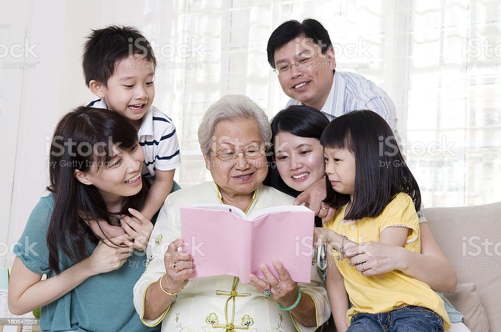Grandmother shows book for three grandsons and two parents royalty-free stock photo