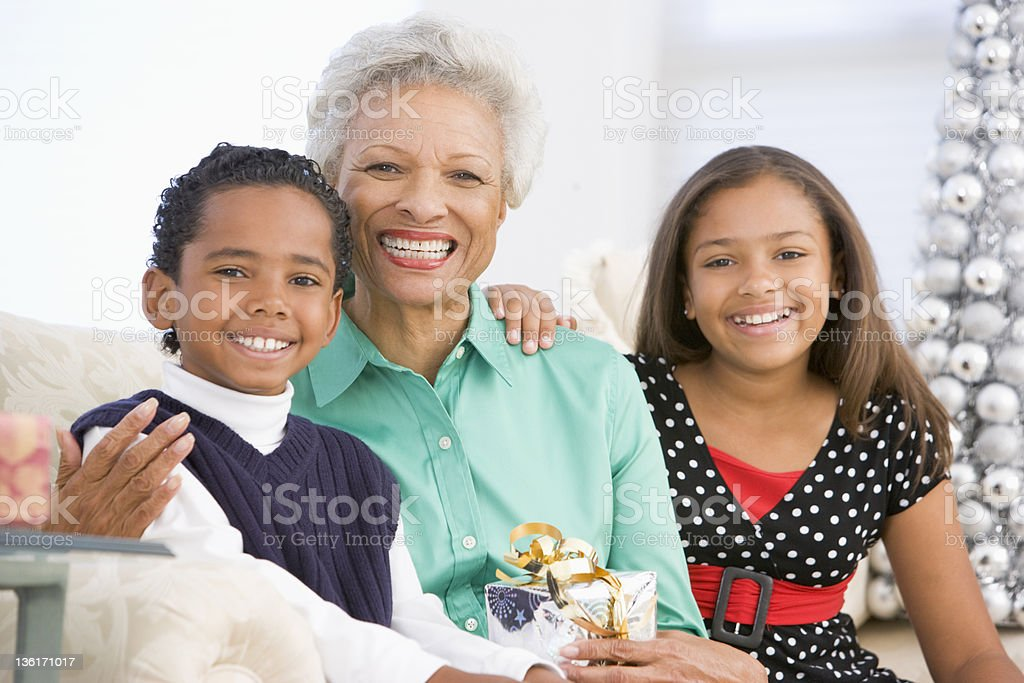Grandmother Sitting With Her Two Grandchildren Holding A Christmas Gift royalty-free stock photo