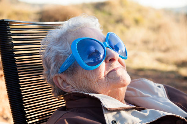 Grandmother sunbathing with pretty glasses stock photo