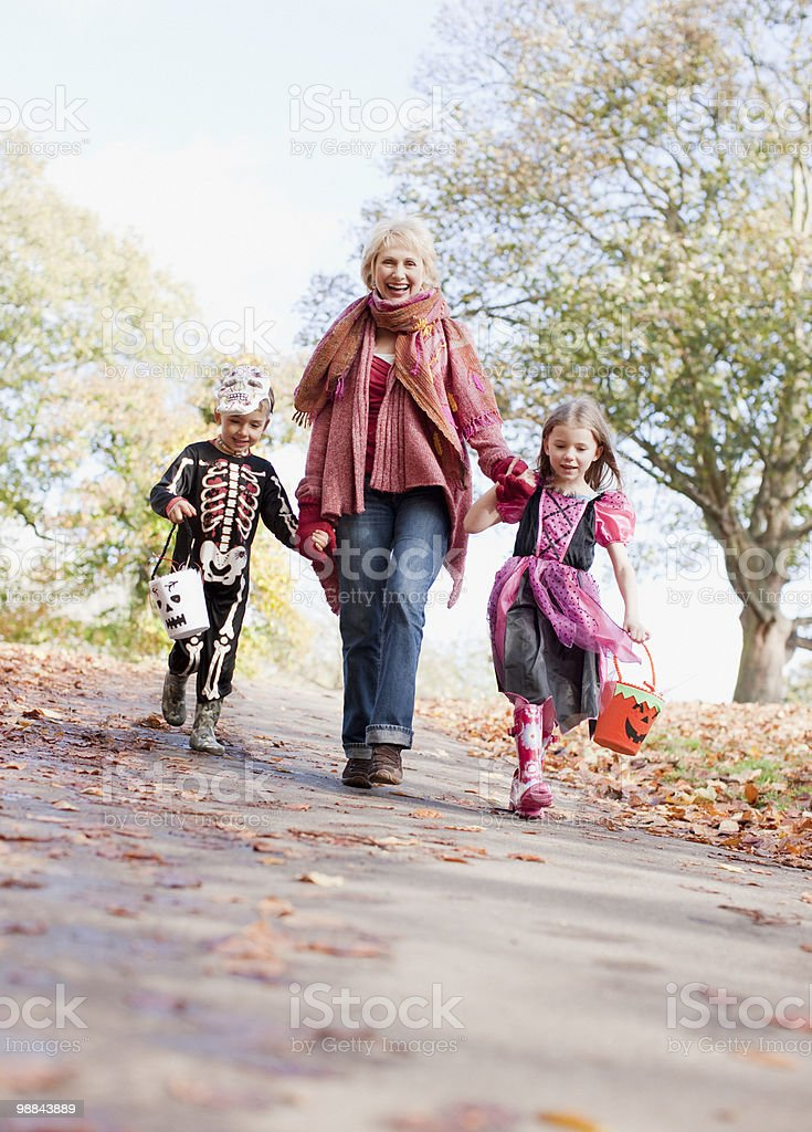 Grandmother taking grandchildren trick or treating 免版稅 stock photo