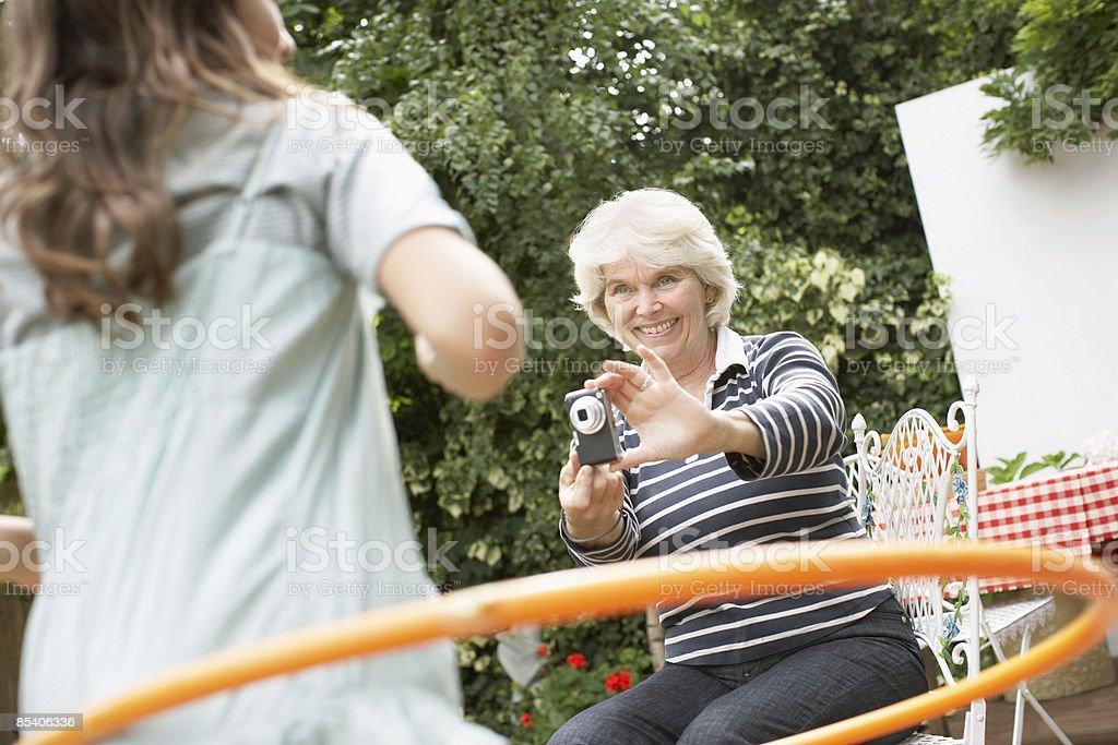 Grandmother taking photograph of granddaughter using hula hoop royalty-free stock photo