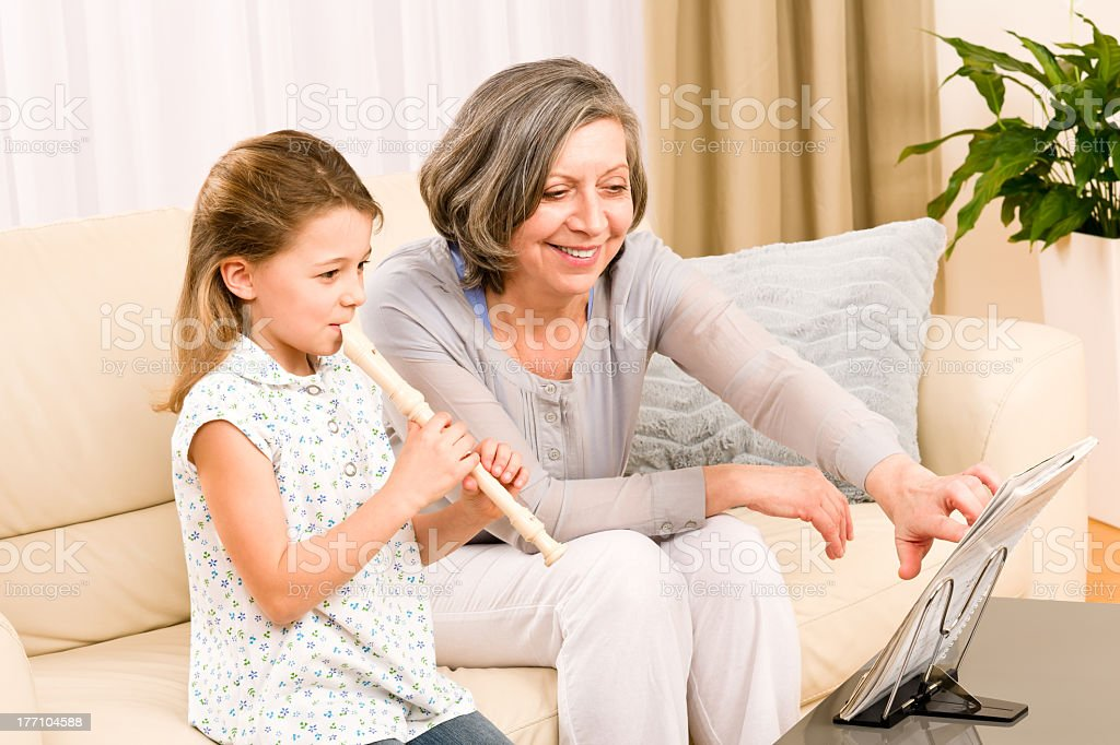 Grandmother teach young girl play flute happy royalty-free stock photo
