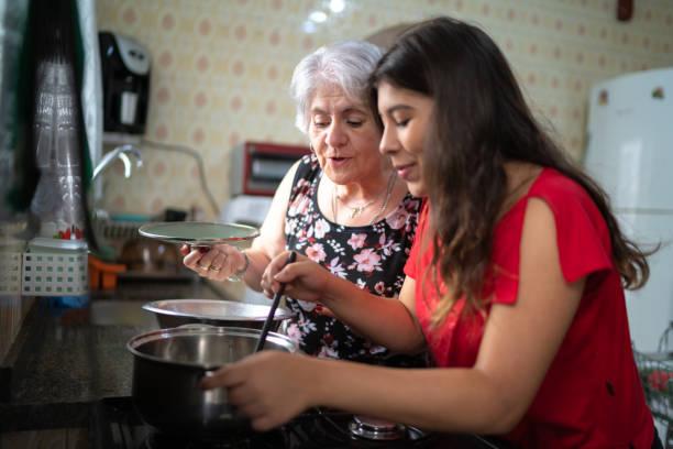 nonna che insegna a sua nipote come cucinare - cucinare foto e immagini stock