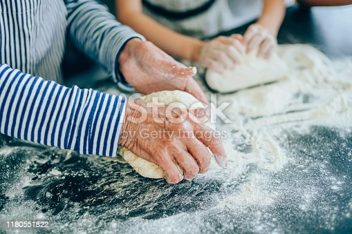 Close-up of wrinkled hands of older woman and child hands kneading dough