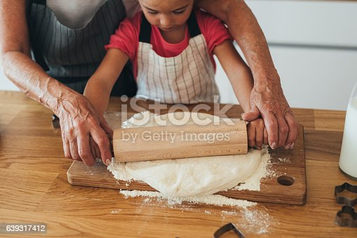 istock Grandmother teaching her granddaughter to roll out dough 639317412
