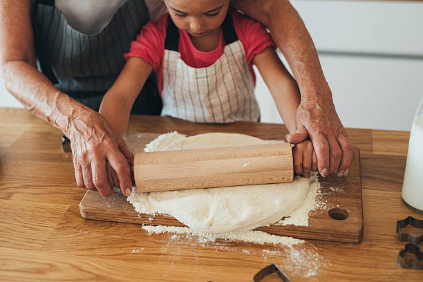 grandmother teaching her granddaughter to roll out dough - 반죽 활동 뉴스 사진 이미지