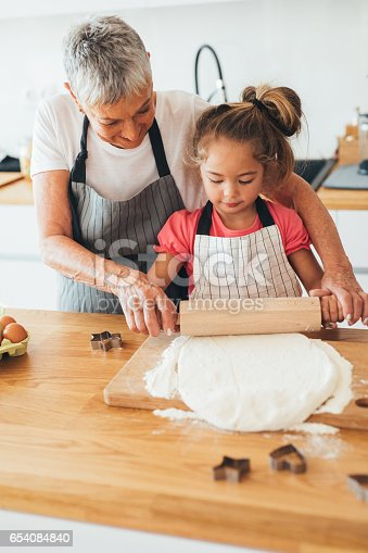 istock Grandmother teaching her granddaughter to roll out dough 654084840